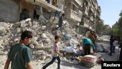 Warga mengangkut barang-barang dari lokasi permukiman yang terkena serangan udara di distrik al-Qaterji, Aleppo, Suriah (17/10).