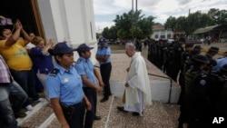 El padre Edwin Román cruza de regreso el cerco policial alrededor de su parroquia tras intentar convencer a la policía que permita el ingreso a familiares de reos políticos, el pasado 14 de noviembre. Foto VOA