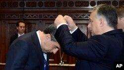 Bulgarian President Rosen Plevneliev, left, is awarded with the Grand Cross of the Hungarian Order of Merit with Chain and Star with Golden Beams by Hungarian Prime Minister Viktor Orban in the Parliament building in Budapest, Hungary, Nov. 10, 2016.
