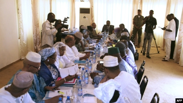 Mali's interim president, Dioncounda Traore (Back center R), speaks with ministers during a cabinet meeting at which a national state of emergency was declared, in Bamako, January 11, 2013.