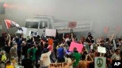 亚利桑那州菲尼克斯的警察在该市会展中心外使用催泪瓦斯后,抗议的人群朝他们大喊(2017年8月22日)