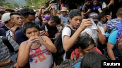 Honduran migrants, part of a caravan trying to reach the U.S., drink water after arriving to the border between Honduras and Guatemala, in Agua Caliente, Guatemala, Oct. 15, 2018.