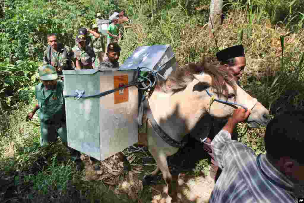 Electoral workers, escorted by police officers and soldiers, use horses to transport ballot boxes to polling stations in remote areas in Tlogosari, East Java, Indonesia. The world's third-largest democracy prepares to elect a new president on July 9.