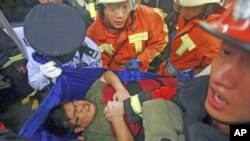 Rescue workers evacuate an injured man from a train after a subway train collision near Yu Yuan Garden station in Shanghai, China, September 27, 2011.