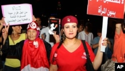 Tunisian women carry placards protesting their rights.