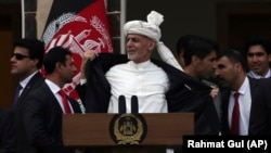 Afghan President Ashraf Ghani, center, opens his coat after a few rockets are fired during his speech after being sworn, at his inauguration ceremony at the presidential palace in Kabul, Afghanistan, Monday, March 9, 2020.