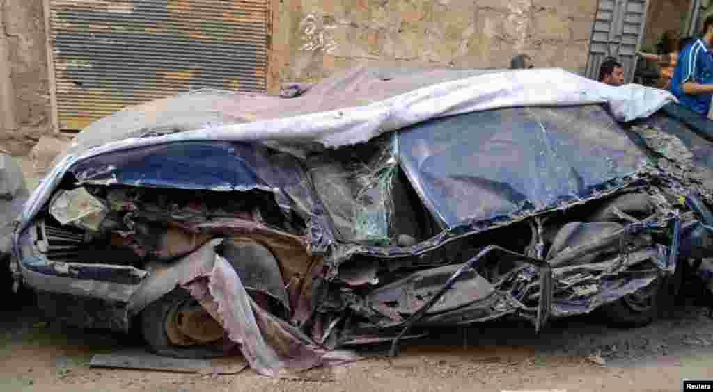 A destroyed car along a street in Deir Al Zour, May 15, 2012.