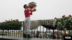 El jockey peruano José Valdivia Jr.disfruta del momento con el trofeo de ganador del Belmont Stakes, en Elmont, Nueva York.