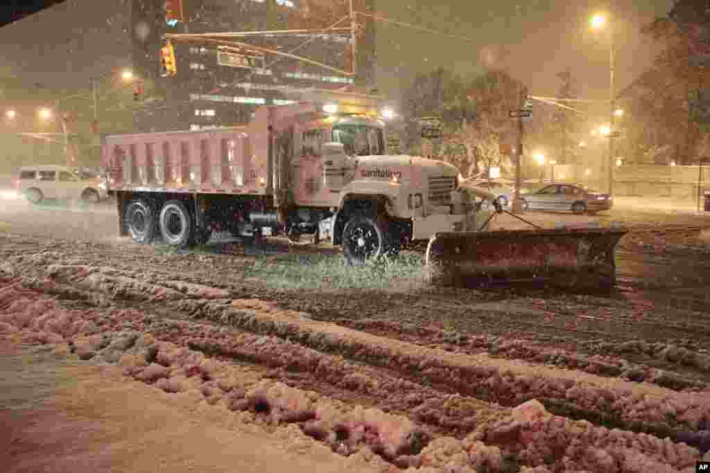 Workers shovel snow from Queens Blvd. during a snow storm, November 7, 2012, in New York.