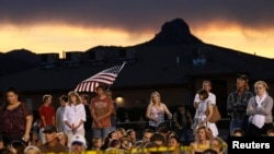 People listen at a prayer vigil ceremony for the 19 firefighters killed in a nearby wildfire in Prescott, Arizona, July 2, 2013.