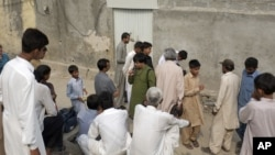 People gather outside the locked house of a Christian girl who was arrested in the suburbs of Islamabad, Aug. 20, 2012.