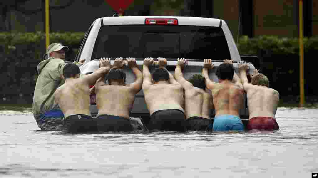 Des habitants de Houston poussent un pick-up bloqué dans une rue inondée, le 27 août 2017.