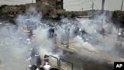 Des Palestiniens tentant d'échapper aux gaz lacrymogènes des forces israéliennes, Jérusalem, le 21 juillet 2017.