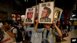 Demonstrators holding posters of Mexico's President Enrique Pena Nieto, right, and Attorney General Jesus Murillo Karam, left, march in protest against the disappearance of 43 students in the state of Guerrero, in Mexico City, Nov. 5, 2014.