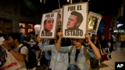Demonstrators holding posters of Mexico's President Enrique Pena Nieto, right, and Attorney General, Jesus Murillo Karam, left, march in protest for the disappearance of 43 students in the state of Guerrero, in Mexico City, Nov. 5, 2014.