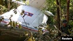 Một nhân viên cứu hộ đứng gần đống đổ nát của chiếc máy bay quân sự AN 74-300, gần làng Nadee, tỉnh Xiengkouang, 17/5/2014.