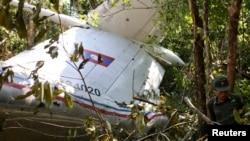 Seorang petugas tengah memeriksa pesawat militer yang jatuh dekat desa Nadee, provinsi Xiang Khouang, Laos utara (17/4).