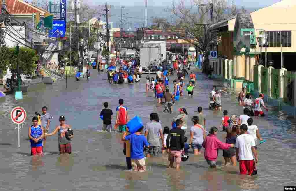 """ساکنان شهر نابوا فیلیپین در آبهای سیل راه میروند. این سیل نتیجه توفان """"ناک تن"""" است."""