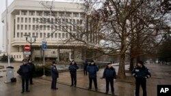Украинские полицейские охраняют улицу перед зданием местного органа власти в Симферополе. Крым, Украина, 27 февраля 2014г.