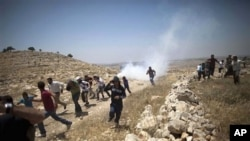 Palestinians run from tear gas fired by Israeli soldiers during a demonstration against the expansion of nearby settlements at the West Bank village of Dier Qadis, near Ramallah, June 15, 2011.