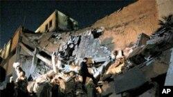 연합군의 폭격으로 파괴된 리비아 수도 트리폴리 인근에 있는 무아마르 카다피의 관저에서 카다피 지지자들이 건물 잔해를 살피고 있다.