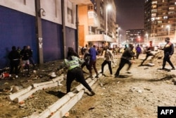 FILE - South Africa Police Services (SAPS) officers stop looters from looting in central Durban, July 11, 2021.