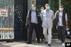 FILE - Hong Kong media tycoon Jimmy Lai, center, who founded local newspaper Apple Daily, is arrested under the new national security law by police officers at his home, Aug. 10, 2020.