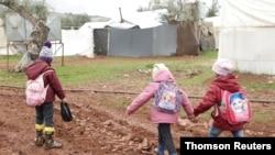 Des enfants syriens déplacés marchent dans la boue près de tentes dans un camp au nord d'Alep, près de la frontière avec la Turquie.