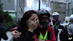 A woman cries as she pleads with the police not to beat a man as police detain protesters calling for electoral reforms and a boycott of the Chinese Communist Party in Hong Kong, Sunday, Jan. 19, 2020. Hong Kong has been wracked by often violent anti…