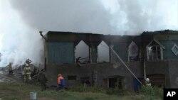 Para petugas berupaya memadamkan api di rumah sakit jiwa di desa Luka, wilayah Novgorod, Rusia, Jumat pagi (13/9).