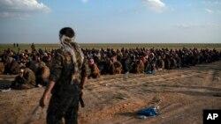 Kombatan Pasukan Demokratik Suriah yang didukung AS, berjaga di dekat para pria yang menunggu untuk diperiksa setelah dievakuasi dari wilayah terakhir ISIS, dekat Baghuz, timur Suriah, 22 Februari 2019.