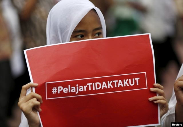 "An elementary school student holds a placard reading ""Students are not afraid"" at a small anti-terrorism rally in central Jakarta a day after a gun and bomb attack in the city, Jan. 15, 2016."