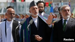 FILE - Afghan President Hamid Karzai (C) speaks during celebrations to commemorate Afghanistan's 95th anniversary of independence as he is flanked by presidential candidates Abdullah Abdullah (R) and Ashraf Ghani in Kabul, Afghanistan, August 2014.