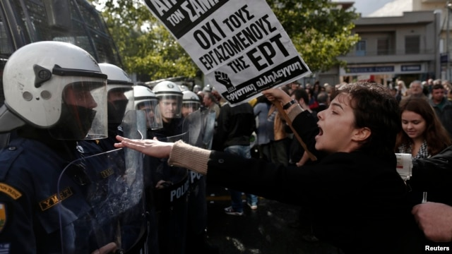 A protester yells at policemen outside the headquarters of Greece's state television ERT, north of Athens, November 7, 2013.