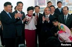 시진핑(왼쪽) 중국 국가주석이 29일 홍콩국제공항에 내린 직후 현지 어린이들의 인사를 받고있다. 마중나온 렁춘잉(왼쪽 두번째) 행정장관과 캐리 람(세번째) 행정장관 당선인 등이 함께 박수하고 있다.