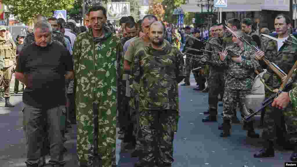 Armed pro-Russian separatists, right, escort a column of Ukrainian prisoners of war as they walk across central Donetsk, Ukraine, Aug. 24, 2014.