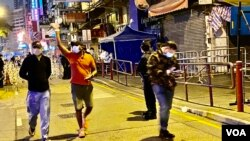 香港政府宣布1月25日傍晚6時開始,持陰性病毒檢測證明的人士,可以登記離開佐敦封鎖區,被禁足接近40小時的居民重獲自由後離開封鎖區時向傳媒揮手。(美國之音湯惠芸)