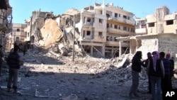 Para pemberontak Suriah berdiri diantara bangunan-bangunan yang hancur akibat serangan udara pasukan pemerintah Suriah di Homs, Suriah (Foto: dok). Tim pemyelidik HAM PBB melaporkan situasi HAM di Suriah yang semakin memburuk, Senin (11/3).