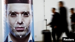 People walk past a poster simulating facial recognition software at the Security China 2018 exhibition on public safety and security in Beijing, China October 24, 2018. (REUTERS/Thomas Peter)