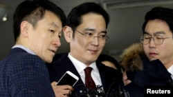 FILE - Jay Y. Lee (center) vice chairman of Samsung Electronics, arrives to be questioned as a suspect in bribery case in the influence-peddling scandal that led to the president's impeachment at the office of the independent counsel in Seoul, South Korea, Jan. 12, 2017.