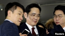 FILE - Jay Y. Lee (center) vice chairman of Samsung Electronics, arrives to be questioned as a suspect in bribery case in the influence-peddling scandal that led to the president's impeachment at the office of the independent counsel in Seoul, South Korea.