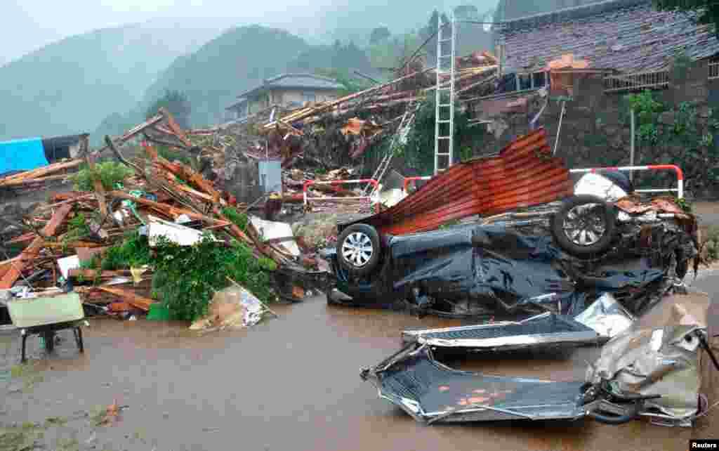 Một chiếc xe bị phá hủy nằm gần ngôi nhà bị sụp đổ vì đất lở sau các trận mưa lớn ở thị trấn Minamiaso trong quận Kumamoto, Nhật Bản