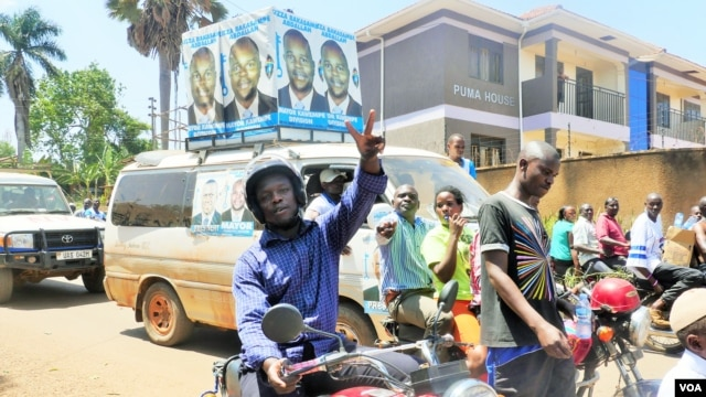 Supporters of opposition leader Kizza Besigye flash the peace sign, or victory sign, to show solidarity with their candidate in the suburb of Ntinda, Uganda, Feb. 16, 2016. (Photo: Lizabeth Paulat for VOA)