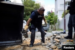 An Israeli police explosives expert carries the remains of a rocket fired from Gaza that landed in Ashdod, Israel, July 14, 2014.