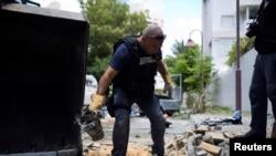 Seorang polisi Israel tengah membawa kepingan roket dari Gaza yang berhasil ditembak dan jatuh di kawasan Ashdod (14/7). Militer Israel mengatakan telah menembak jatuh sebuah drone yang terbang memasuki Israel dari Gaza.