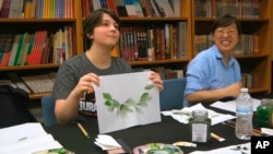 Undergraduate student Moe Lewis, left, shows her watercolor painting of peony leaves at a traditional Chinese painting class at the Confucius Institute at George Mason University in Fairfax, Va., on May 2, 2018. (AP Photo/Matthew Pennington)