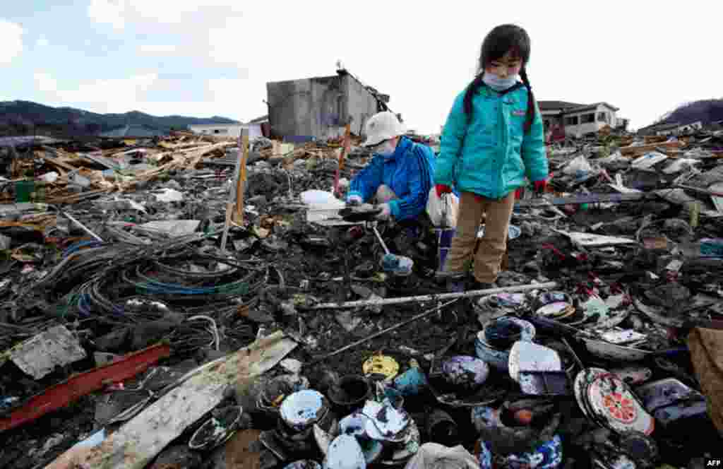 March 23: Tokiko Takada and her granddaughter Mai search through the rubble of their home destroyed by the March 11 tsunami at Kesennuma, northern Japan. (AP Photo/Shizuo Kambayashi)