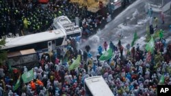South Korean riot police officers spray water cannons as police officers try to break up protesters who tried to march to the Presidential House after a rally against government policy in Seoul, South Korea, Nov. 14, 2015.