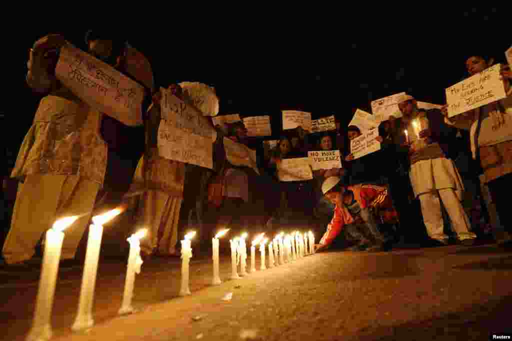 A boy places a candle as demonstrators hold placards during a candlelight march for a gang rape victim, who was assaulted in New Delhi, January 16, 2013.