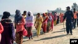 Members of the coast guard escort Rohingya refugees after their boat capsized, in Teknaf, near Cox's Bazar, Bangladesh, Feb. 11, 2020.